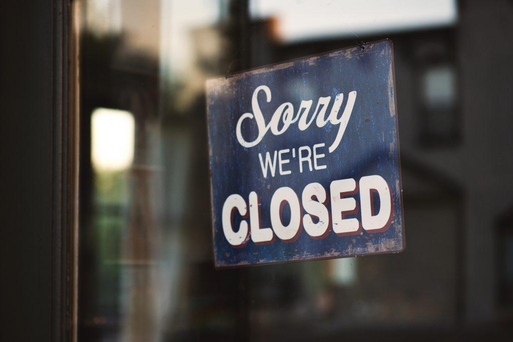 """Schild auf dem steht """"Sorry we're closed"""" hängt in einer Tür."""