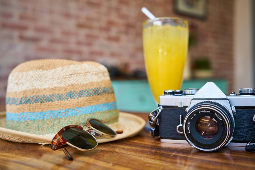 Sonnenhut, Sonnenbrille, Kamera und Cocktail liegen auf einem Tisch.