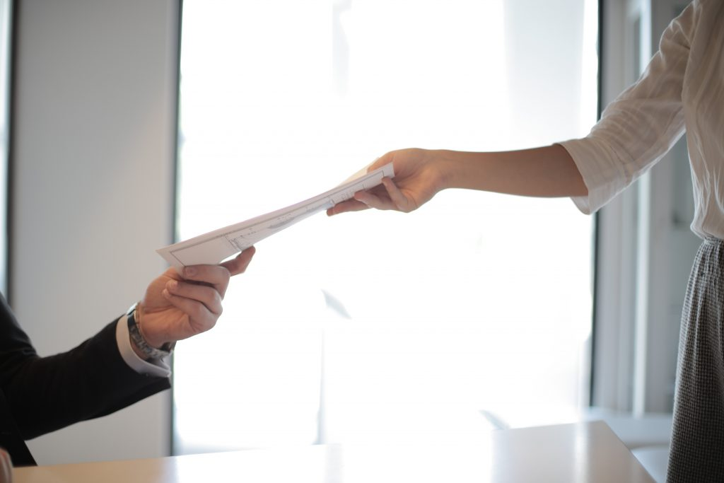 Eine Person überreicht einer anderen ein Dokument.