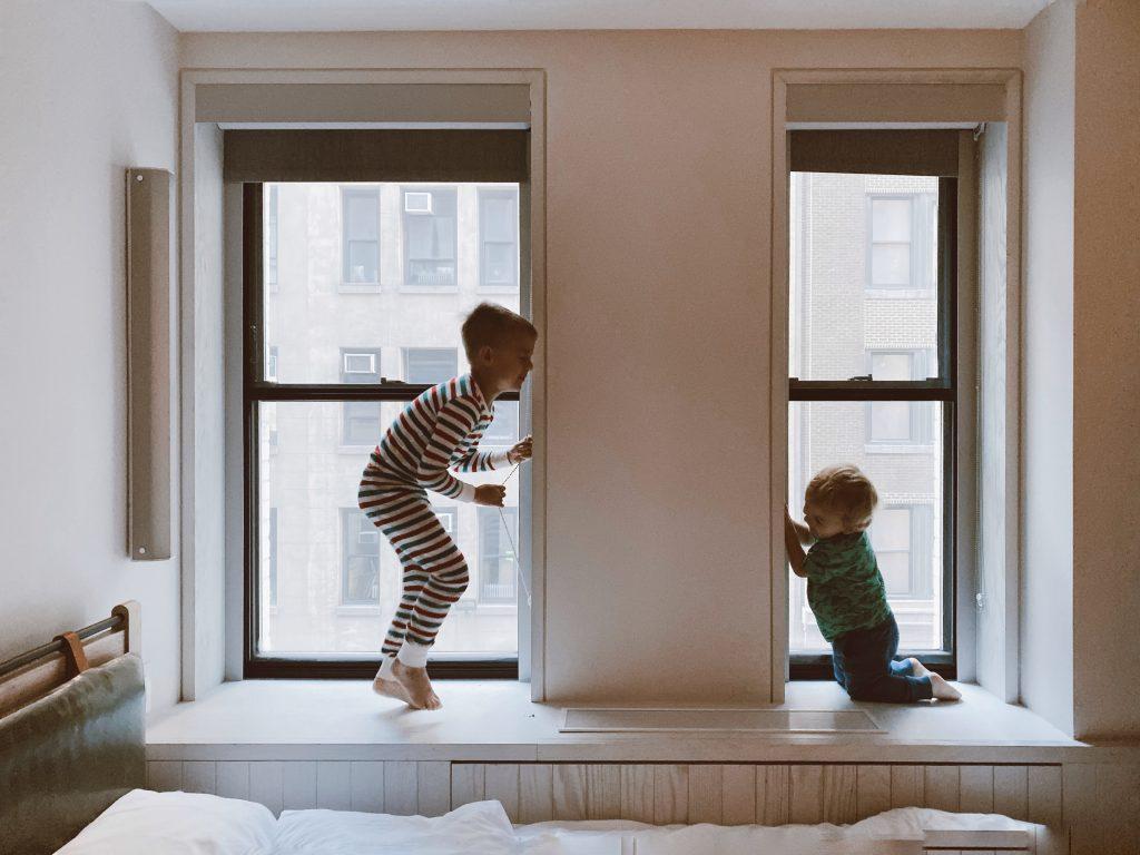 Zwei Kinder spielen am Fenster